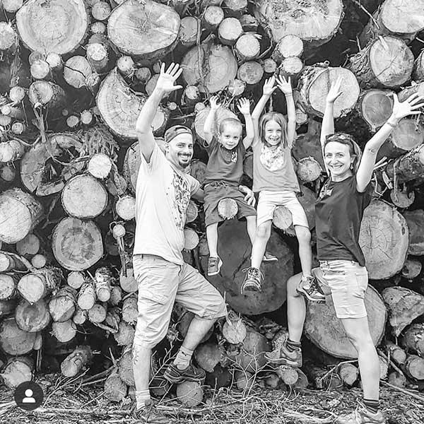 mamma papà e due bimbi davanti a catasta di legna