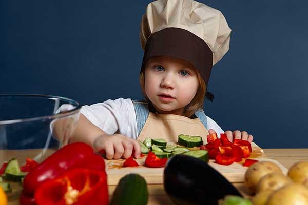 bambina con cappello da cuoco e verdure