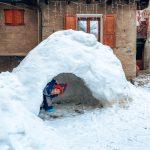 Bambino in un igloo di neve