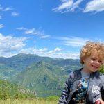 bambino seduto su una staccionata durante una passeggiata in Lombardia