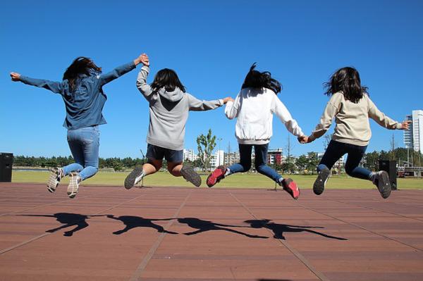 bambine che saltano tenendosi per mano